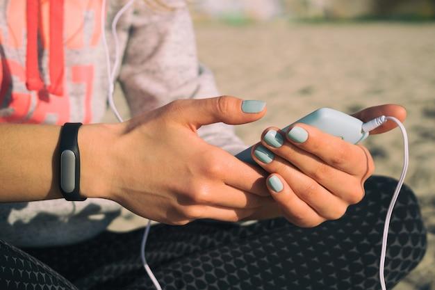 Garota na praia em roupas esportivas ouvir música com fones de ouvido em um smartphone