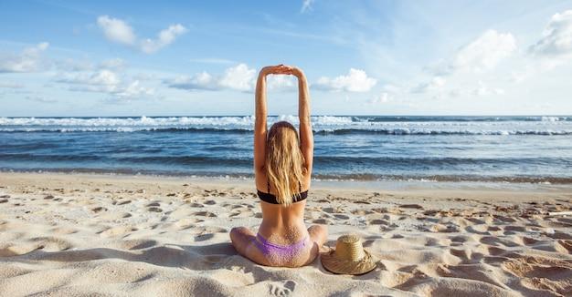 Garota na praia se espreguiçando, sentando-se de costas para a câmera e esticando as mãos para cima