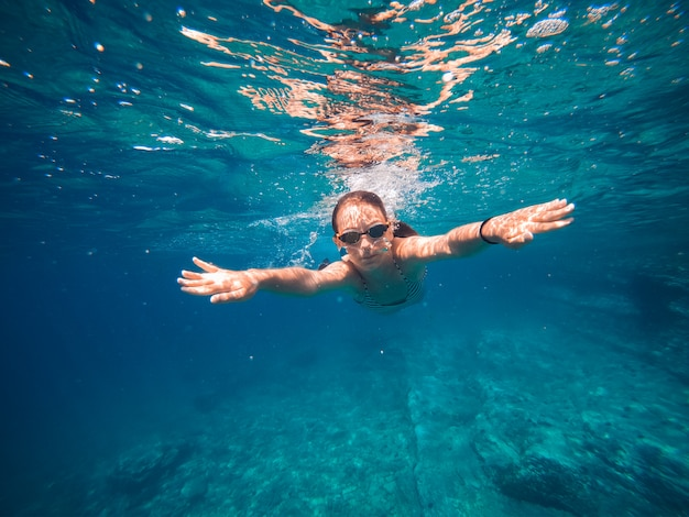 Garota nadando na água rasa do mar