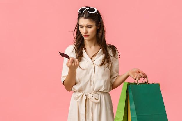 Garota não entende onde todo o dinheiro vai. perfeito e confuso shoppaholic feminino segurando sacolas de compras e olhando sério para cartão de crédito, rosa sem noção