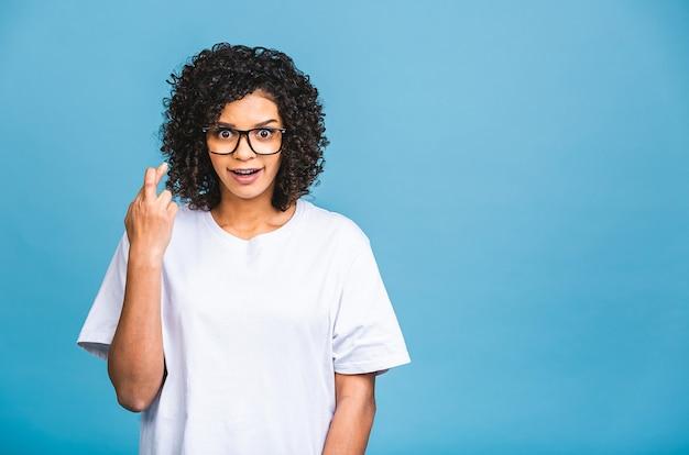 Garota negra afro-americana cruzando os dedos para dar sorte, ganhando a expectativa da loteria, esperança islated sobre fundo azul.