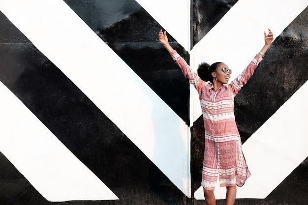 Garota negra afro-americana se divertir perto de portão enorme despojado.