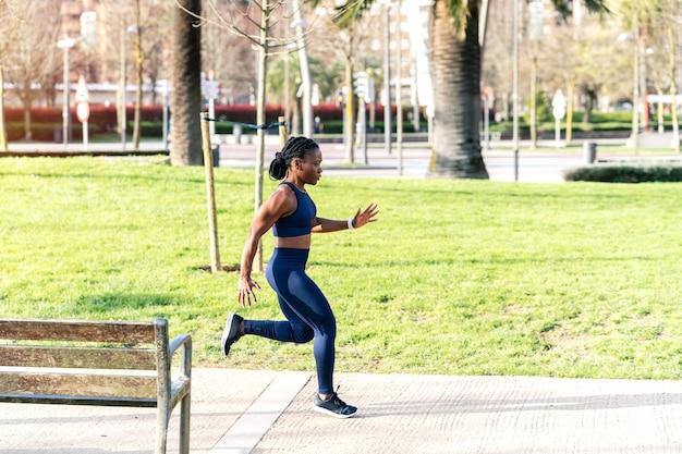 Garota negra afro correndo em um parque público ao pôr do sol