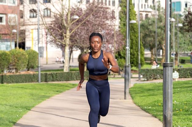 Garota negra afro correndo em um parque público vestida de corredora