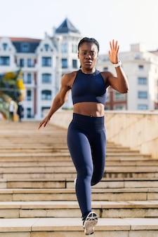 Garota negra afro vestida como uma corredora descendo um lance de escadas na cidade ao pôr do sol