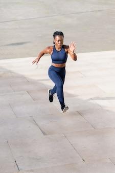 Garota negra afro vestida como uma corredora subindo um lance de escadas na cidade ao pôr do sol