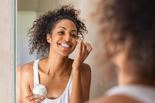 Garota negra, aplicar loção no rosto