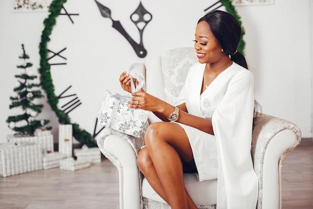 Garota negra elegante em uma sala no natal