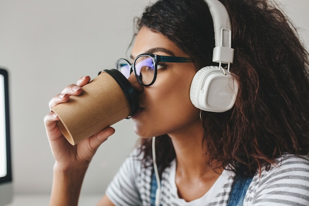 Garota negra elegante usando camisa listrada tomando café