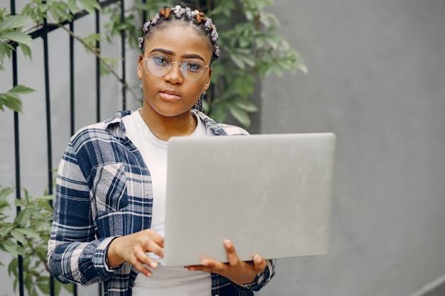 Garota negra em uma cidade de verão com laptop