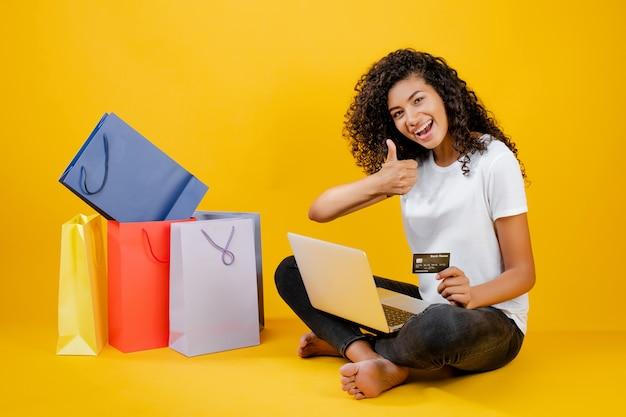 Garota negra feliz com sacolas coloridas, sentado com laptop e cartão de crédito isolado sobre amarelo