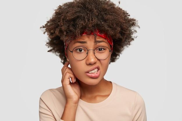 Garota negra incerta e intrigada franze a testa em desgosto, sente apatia, olha com incerteza, não consegue encontrar solução e saída para o problema, tem corte de cabelo afro, modelos contra parede branca. expressão facial