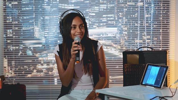 Garota negra no fone de ouvido cantando no microfone.