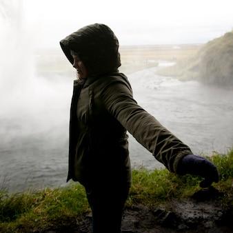Garota no casaco com capuz, em pé de perfil com braços abertos antes de corpo cheio de água