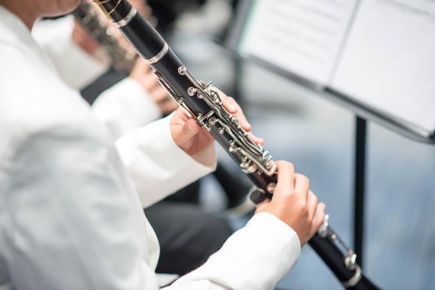 Garota no clarinete atuando na sinfonia do vento no palco Foto Premium