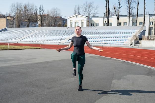 Garota no estádio. garota de esportes em um sportswear. senhora com corda de pular