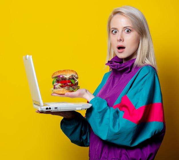 Garota no estilo de roupas dos anos 80 com hambúrguer e notebook, fazendo um pedido