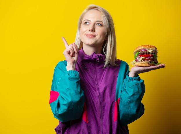 Garota no estilo de roupas dos anos 80 com hambúrguer