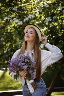 Garota no prak para passear com um buquê de lilases no verão. ela está feliz e sorridente. chapéu