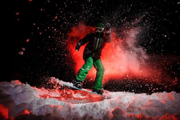 Garota no snowboard vestida com uma roupa esportiva verde, pulando na neve à noite sob a luz vermelha