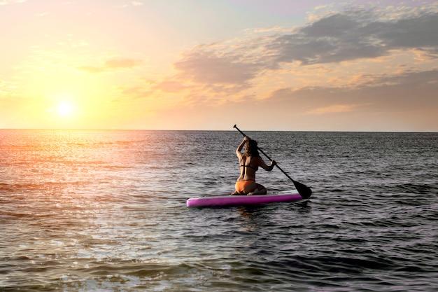 Garota no sup de paddleboard, mar com cores quentes por do sol