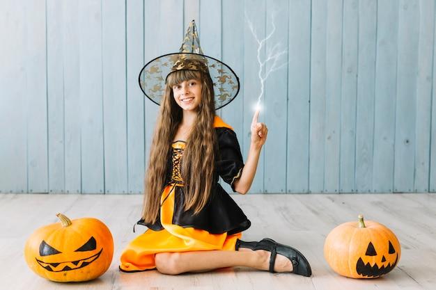 Garota no traje de halloween, sentada no chão e conjurando