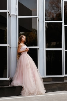 Garota no verão de vestido rosa casamento urbano em um espaço preto