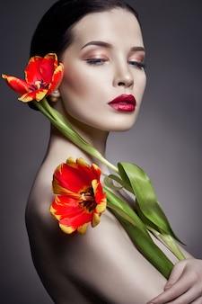 Garota nua nua com flores tulipas na mão e pele perfeita, mulher morena nua sexy. cuidados com a pele do rosto e mãos no verão. maquiagem natural brilhante