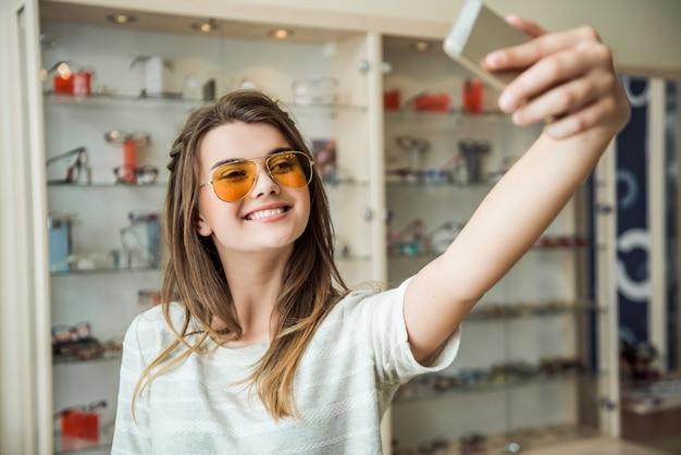 Garota nunca mora em casa sem smartphone, elegante morena europeia experimentando óculos de sol enquanto toma selfie no telefone, sorrindo amplamente
