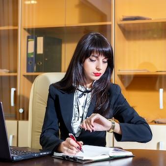 Garota ocupada trabalhando no escritório e olhando para o relógio