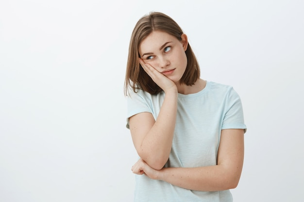 Garota odeia assistir a aulas chatas na universidade, rosto inclinado na mão, revirando os olhos de tédio e aborrecimento em pé indiferente e descontente sobre uma parede cinza em uma camiseta da moda