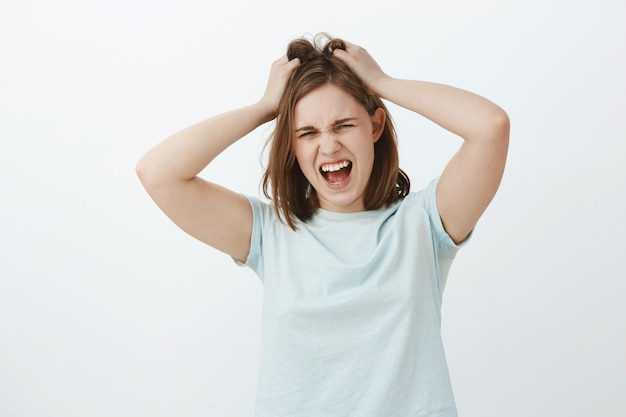 Garota odeia pensar muito. desagradada, angustiada, jovem, chateada, mulher europeia com corte de cabelo castanho curto, gritando enquanto perdia a paciência estando com raiva ou zangada bagunçando ou puxando o cabelo da cabeça
