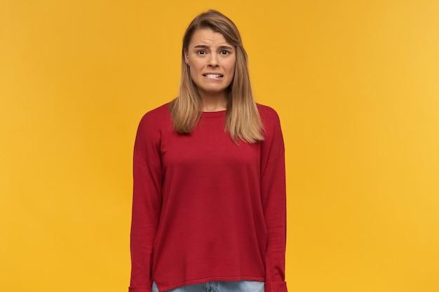 Garota olha olha com nojo, franze a testa, boca aberta, mantém celular na mão, tela preta voltada para a câmera, aponta com o dedo indicador