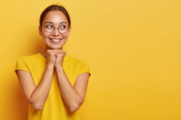 Garota oriental feliz olha de lado com alegria, segura as mãos embaixo do queixo, encantada e sonhadora, focada de lado, tem cabelo escuro, usa óculos e camiseta, isolada em parede amarela com espaço vazio