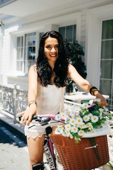Garota oriental sentada na bicicleta com flores no fundo, casa no fundo, verão