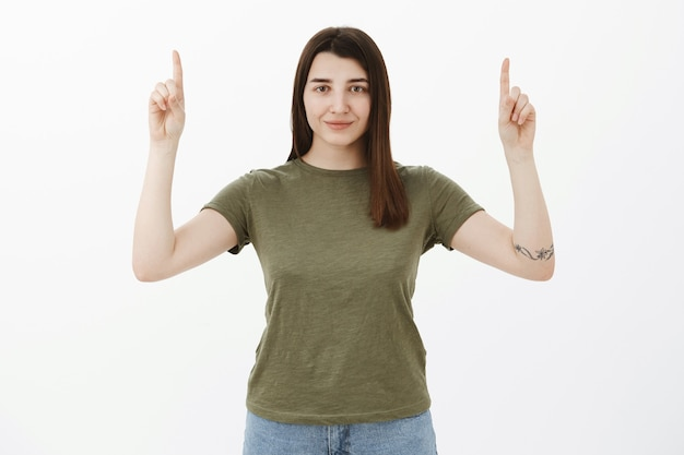 Garota otimista confiante e ambiciosa, bonita, com cabelo castanho e tatuagem, sorrindo autoconfiante e assertiva levantando as mãos e apontando para cima pedindo para dar uma olhada no espaço de cópia sobre a parede cinza