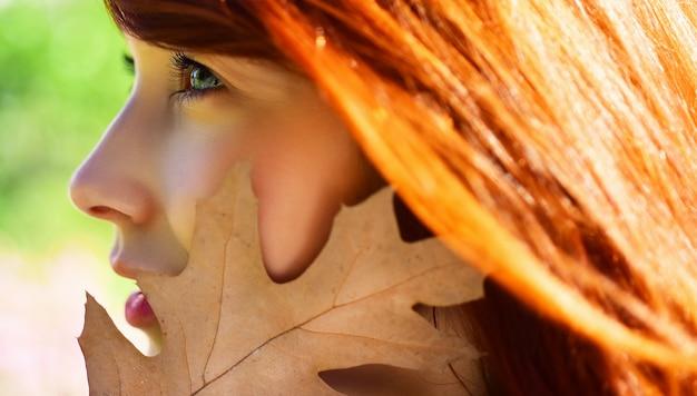 Garota outono fechar retrato. olhos de mulher com folhas de bordo amarelas no fundo da natureza.