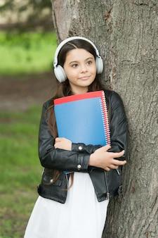 Garota ouvindo áudio carregam livros didáticos relaxante fundo do parque, conceito de lista de reprodução da biblioteca.