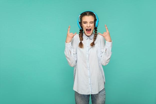 Garota ouvindo música favorita com fone de ouvido, olhando para a câmera com cara de surpresa e sinal de pedra