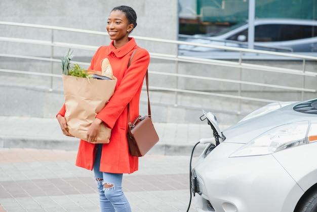 Garota parada perto do carro.