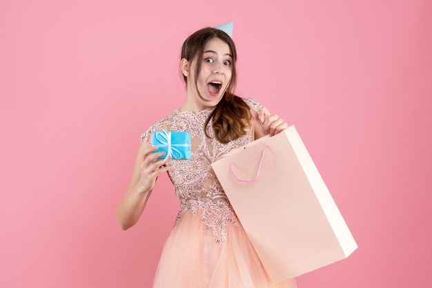 Garota pasma de frente com boné de festa segurando um presente e uma bolsa