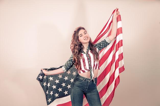 Garota patriótica com a bandeira da américa em uma parede colorida