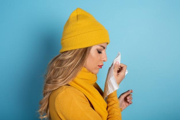 Garota pegou um resfriado e enxuga o nariz. fundo ciano