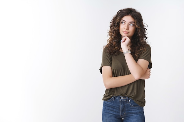 Garota pensando em como administrar melhor o tempo, fazer planos, lista de compras, olhar pensativo, tocar o queixo, sonhar, tomar decisões importantes, fazer escolhas, ficar de pé, fundo branco inseguro
