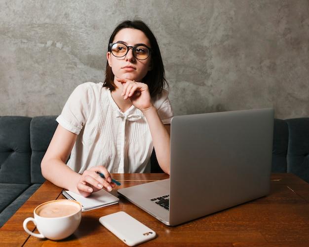 Garota pensando na frente do laptop