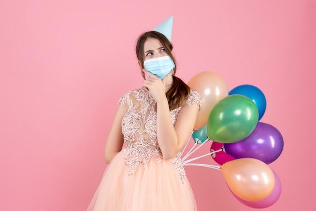 Garota pensativa com boné de festa segurando balões coloridos nas costas em rosa