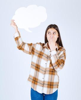 Garota pensativa com nuvem de texto vazio cobrindo a boca na parede branca.
