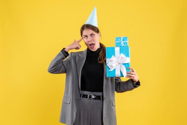 Garota pensativa de vista frontal com chapéu de festa segurando presentes de natal
