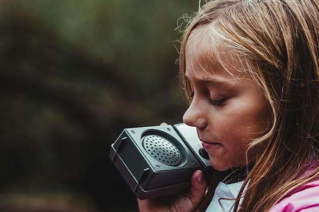 Garota perdida na floresta em um dia chuvoso, tentando se comunicar por gps com seu telefone gps