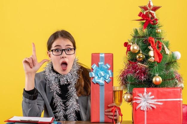 Garota perplexa com óculos de frente, sentada à mesa, apontando com o dedo para a árvore de natal e coquetel de presentes